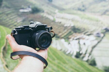 Hand holding black vintage film camera with Sapa rice terraces on background, Vietnam Banco de Imagens