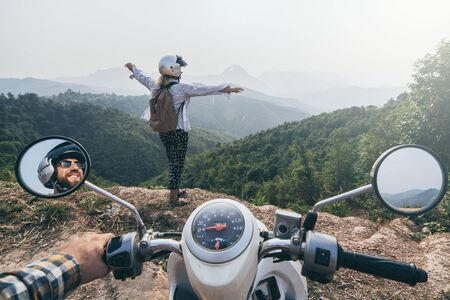 Young Caucasian couple riding a motorcycle in Laotian mountains. Woman standing on cliff edge, hands up. Nong Khiaw village, Laos