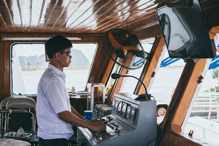 Hanoi, Vietnam - May 2019: Vietnamese captain behind ferry wheel cruising Halong bay.