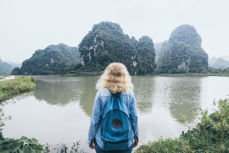 Caucasian blonde woman overlooking limestone mountains in Ninh Binh province, Vietnam. Cloudy day, view from the back, reflection in water Imagens