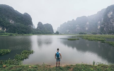 Caucasian man overlooking limestone mountains in Ninh Binh province, Vietnam. Cloudy day, reflection in water Imagens