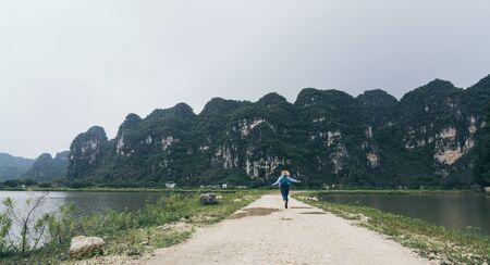 Caucasian blonde woman running towards llimestone mountains in Ninh Binh province, Vietnam. Imagens