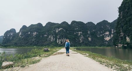 Caucasian blonde woman walking towards llimestone mountains in Ninh Binh province, Vietnam.