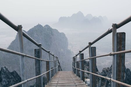 Mountain peak with empty stairs going down during sunrise foggy morning in Hpa-An, Myanmar.