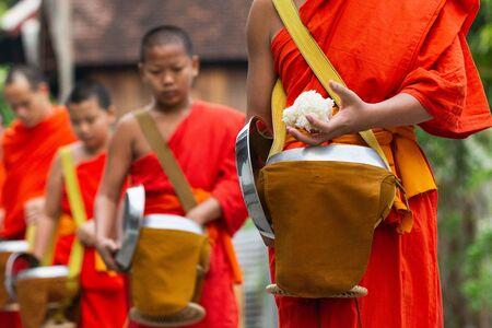 Luang Prabang, Laos - May 2019: Laotian Buddhist monks walking along the street during morning alms giving ceremony Editöryel