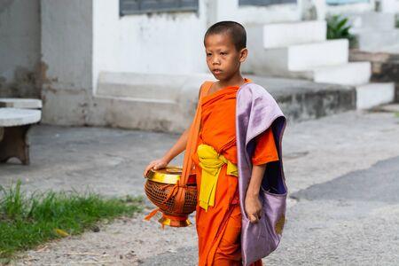 Luang Prabang, Laos - May 2019: Laotian Buddhist monk walking along the street during morning alms giving ceremony