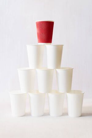 Red paper coffee cup stands on top of white paper cups pyramid. White background, copy space, vertical orientation