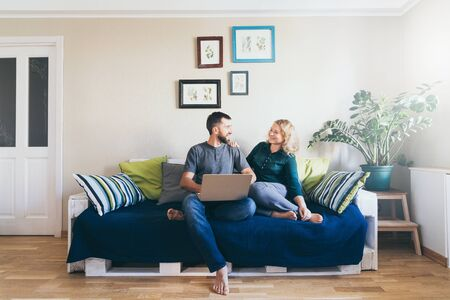 Young Caucasian couple doing shoppings online on the couch at home with laptop, looking at each other and smiling