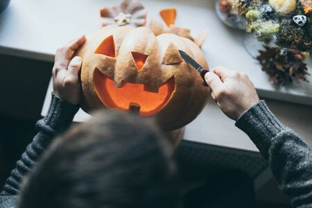 Man cutting pumpkin for Halloween party with a small knife, closeup on hands