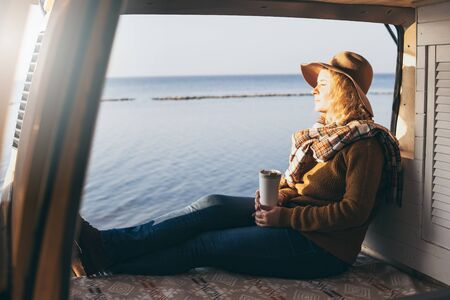 Young blonde Caucasian woman relaxing in her camper van during sunset