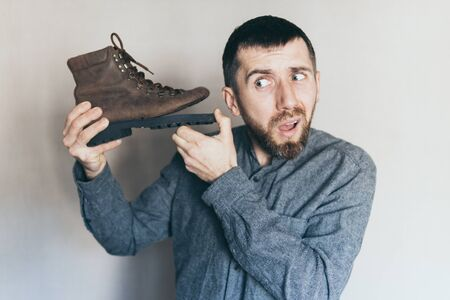 Young bearded Caucasian man holds old leather boot with torn sole, listening, surprise and shock on his face