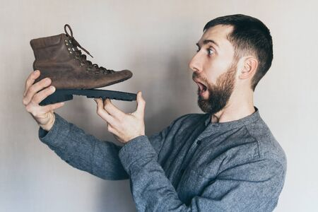 Young bearded Caucasian man looking at an old leather boot with torn sole, surprise and shock on his face