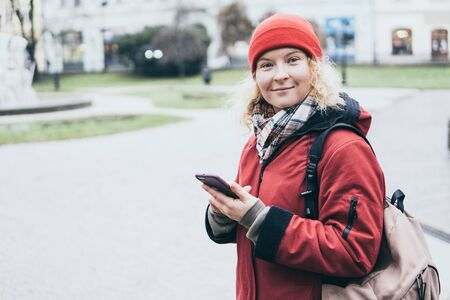 Woman in red coat looking at her mobile phone screen on the street of old European town Stock Photo