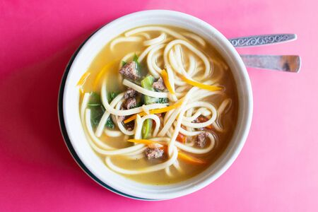 Flat lay of a bowl of Asian noodle soup served with meat and vegetables on pink background