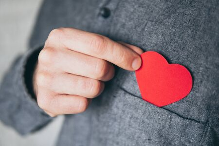 Man taking out red paper heart from the front pocket of his shirt, close up.