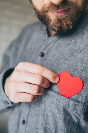 Bearded young man taking out a paper heart from the front pocket of his shirt. Close up, vertical orientation.