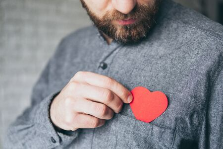 Bearded young man taking out a paper heart from the front pocket of his shirt, close up.