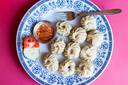 Flat lay still life of Nepalese momo dumplings with yak meat served on a plate with dipping sauce