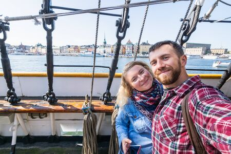 Couple taking selfie with Stockholm waterfront houses through ratlines of sailing ship on background, Sweden