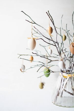 Still life with tree branches decorated with Easter eggs and feathers in a glass vase. Vertical orientation Foto de archivo