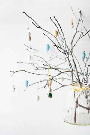 Still life with tree branches decorated with Easter eggs, feathers and bunnies in a glass vase. Vertical orientation