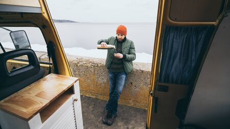 Young man having a hot drink from vacuum flask in front of camper van overlooking a lake on background Banque d'images