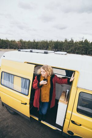Young blond woman travelling by camper van with solar panel on the roof top and pine forest on the background. Vertical orientation