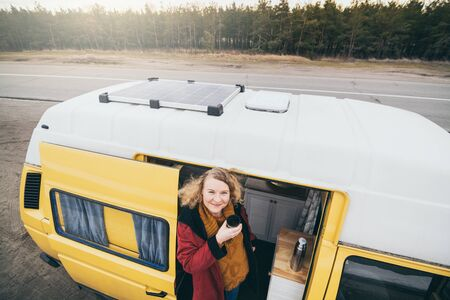 Young blond woman travelling by camper van with solar panel on the roof top and pine forest on the background Banque d'images