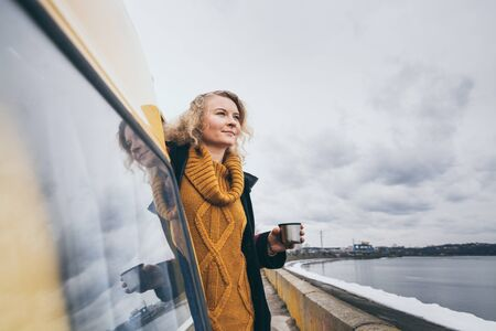 Young blond woman looking out of camper van overlooking the frozen winter sea. Reflection in the car window.