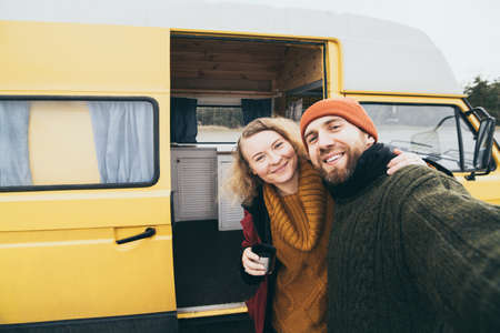Young happy couple taking selfie in front of their yellow camper van