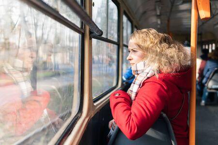 Eastern European blonde woman having a ride in public transport, looking in the window.