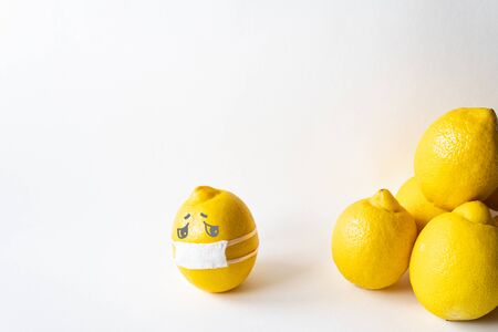Lemon wearing medical mask isolated from the crowd. Conceptual image of social distancing.