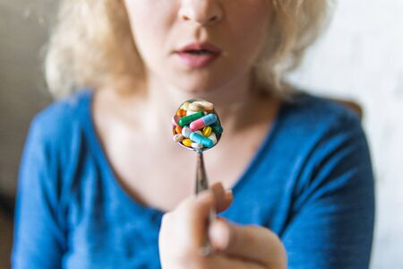 Young blonde woman holding a full spoon of assorted pills in front of her open mouth.