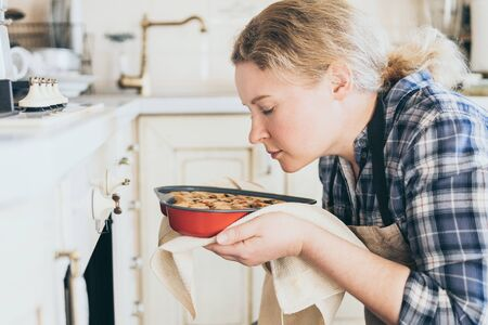Young blonde woman taking heart shaped berry pie out of the oven. Cooking at home and smelling with eyes closed.