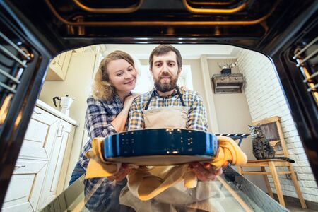 Smiling Eastern European couple cooking at home. Man taking out a pie from the oven with kitchen interior and a cat on background, view from inside the oven.