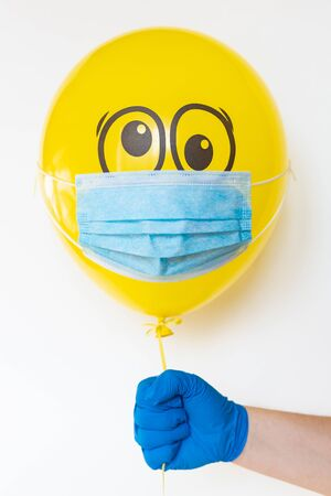 Hand in a rubber glove holding a yellow balloon with a medical mask and doodle shocked eyes. Conceptual image of Birthday party during Corona virus quarantine lockdown