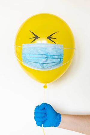 Hand in a rubber glove holding a yellow balloon with a medical mask and doodle closed eyes. Conceptual image of Birthday party during Corona virus quarantine lockdown Banque d'images