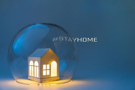 Conceptual image of safety when staying at home during Corona virus COVID-19 quarantine lockdown. Toy house protected by glass bowl with hashtag stayhome on background.