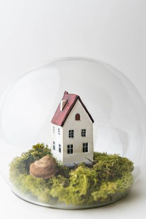 Conceptual image of safety when staying at home during Corona virus COVID-19 quarantine lockdown. Small toy house under the glass with moss and grass around.