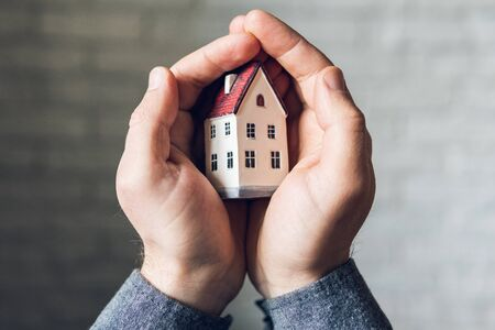 Male hands holding and protecting a small toy house. Conceptual image of insurance and staying home safe during Corona virus COVID-19 quarantine lockdown.