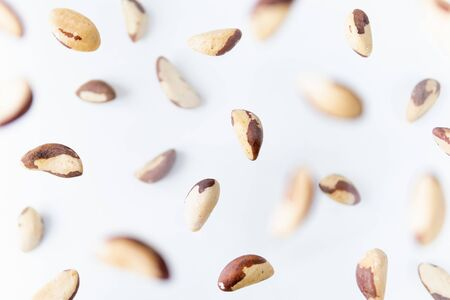 Shelled Brazilian nuts flying above white background, levitation effect. Banque d'images