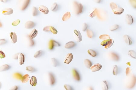 In shell pistachio nuts flying above white background, levitation effect.