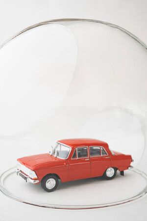 Red toy car inside a glass ball. Conceptual image of insurance coverage and safety protection. Vertical orientation. Banque d'images