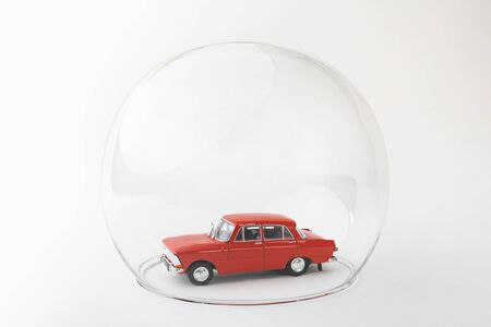 Red toy car inside a glass ball. Conceptual image of insurance coverage and safety protection.