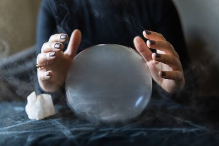 Fortune teller holding hands above magic crystal ball with smoke around. Conceptual image of practicing black magic and occultism. Banque d'images