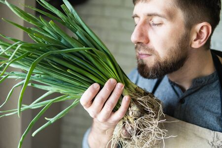 Young man in rustic apron holding and smelling a bunch of green onions. Healthy, vegetarian and organic farm food concept. Banque d'images