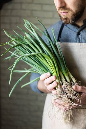 Young man in rustic apron holding a bunch of green onions. Healthy, vegetarian and organic farm food concept.