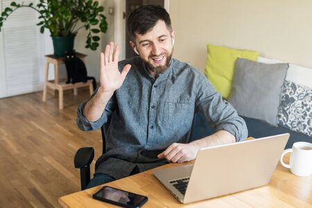 Handsome Eastern European man working from home during Corona virus quarantine lockdown, having online video chat with his colleagues Banque d'images