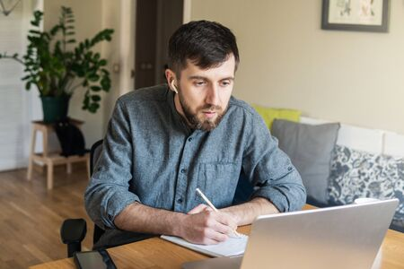 Handsome Eastern European man studying remotely at home during Corona virus quarantine lockdown, writing down during online courses