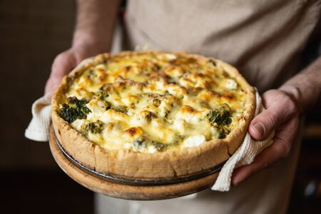 Male hands holding cheese and broccoli quiche tart. Home cooking according to French recipe. Banque d'images